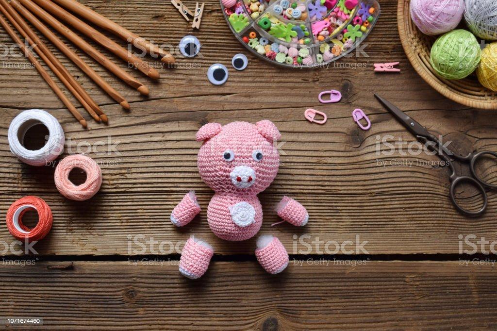 Haciendo el cerdo rosa. Crochet juguetes para el niño. En la tabla hilos, agujas, gancho, hilo de algodón. Paso 1 - punto todos los detalles de juguete. Artesanías hechas a mano. Concepto de DIY. Pequeñas empresas. Ingresos de pasatiempo - foto de stock