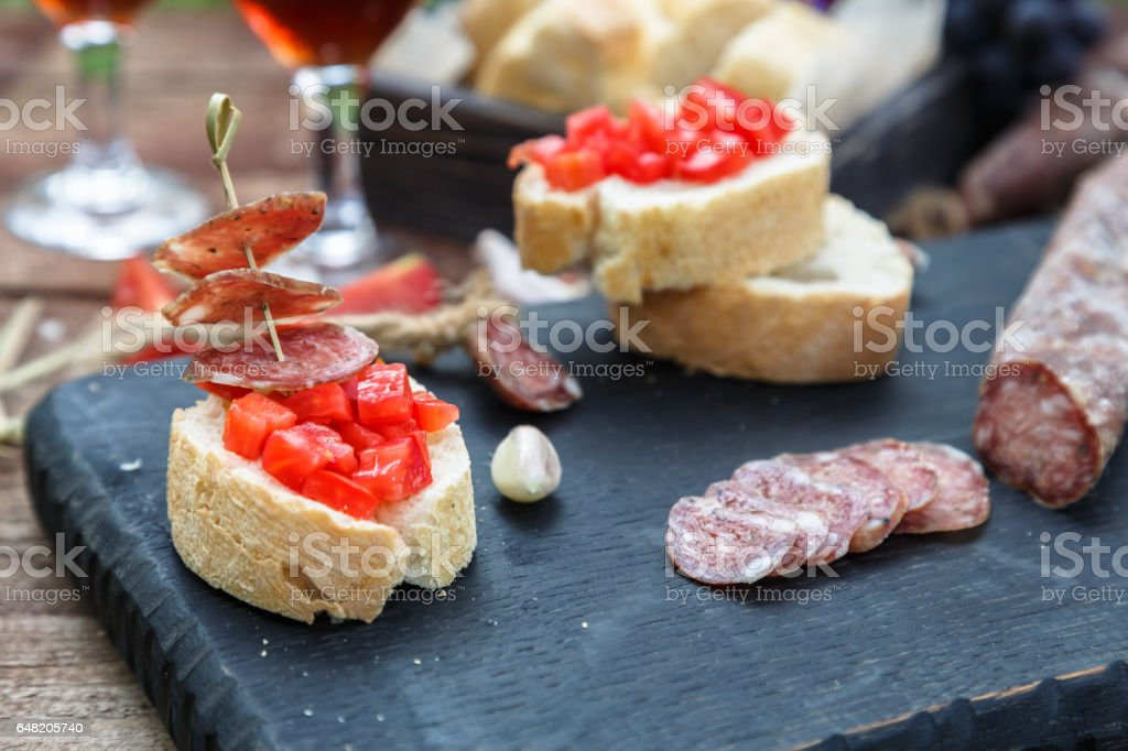 Making pintxo with tomato and sausages, tapas, spanish canapes party finger food stock photo