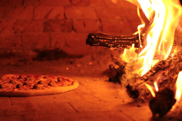 Making pizza in a Masonry oven stock photo