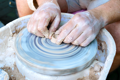 Making pottery on a potter's wheel. Hands craftsman close-up, mold dishes. Master class