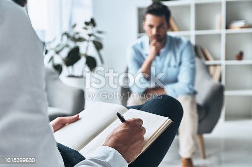 Young frustrated man solving his mental problems while having therapy session with psychologist