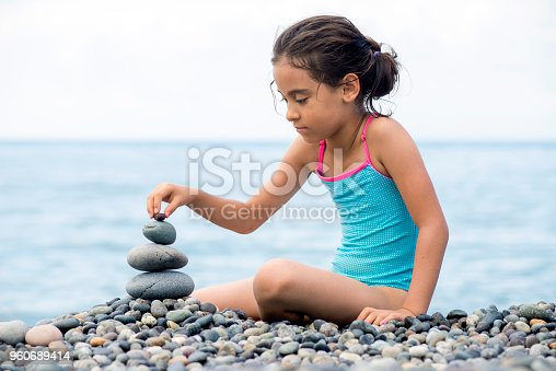 istock Making pyramids from beach pebbles, children's play. Nature and balance concept/ Artvin,Turkey,25 July 2017 960689414