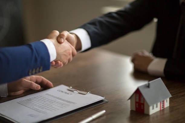making real estate deal, handshake with agent - кредит и кредитные карты стоковые фото и изображения