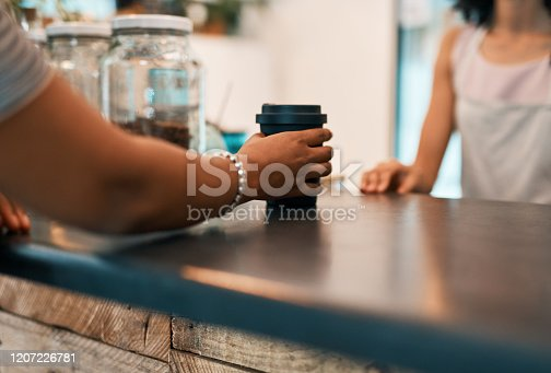 Cropped shot of a woman ordering a drink in a reusable cup at a waste free store