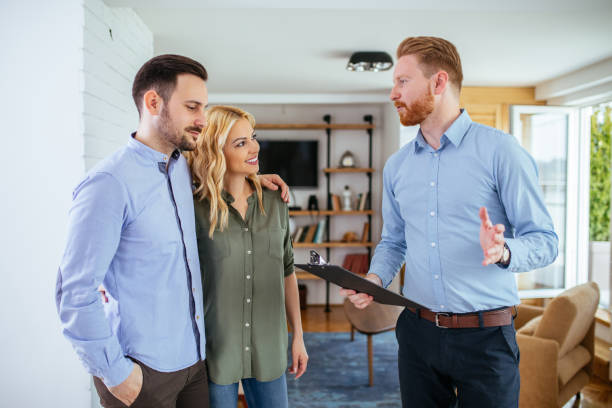 Making responsible decisions about their future Photo of a young couple counseling with financial adviser at home. salesman stock pictures, royalty-free photos & images