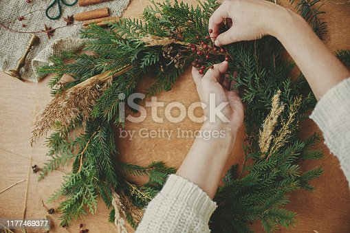 Making rustic Christmas wreath flat lay. Hands holding fir branches, and pine cones, thread, berries, scissors on wooden table. Christmas wreath workshop. Authentic stylish still life