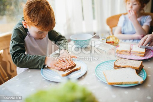 Two children making their sandwiches for lunch.