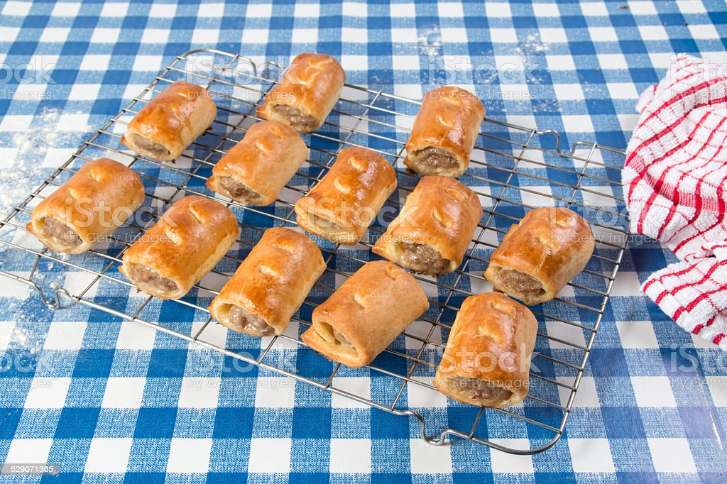 Making sausage rolls, finished sausage rolls baked on cooling rack stock photo