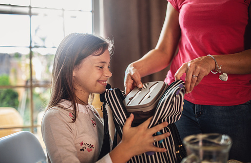 Mother preparing healthy snacks lunch boxes for daughter