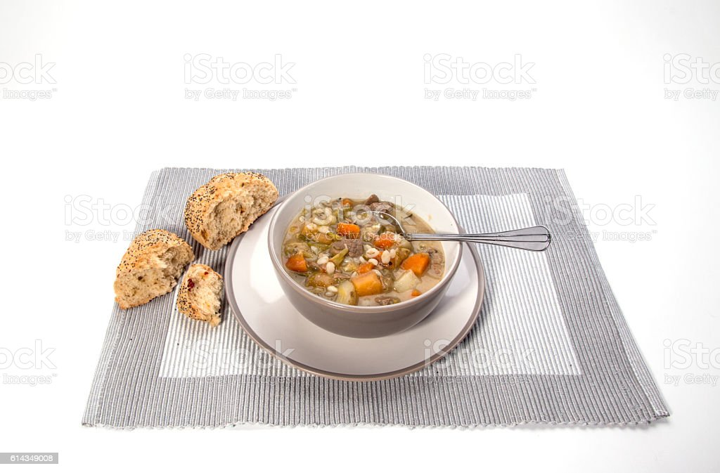 Making Scotch Broth, a taupe coloured bowl with a spoon stock photo