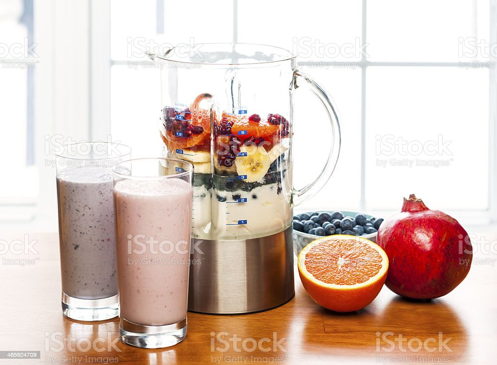 Making smoothies in blender with fruit and yogurt stock photo