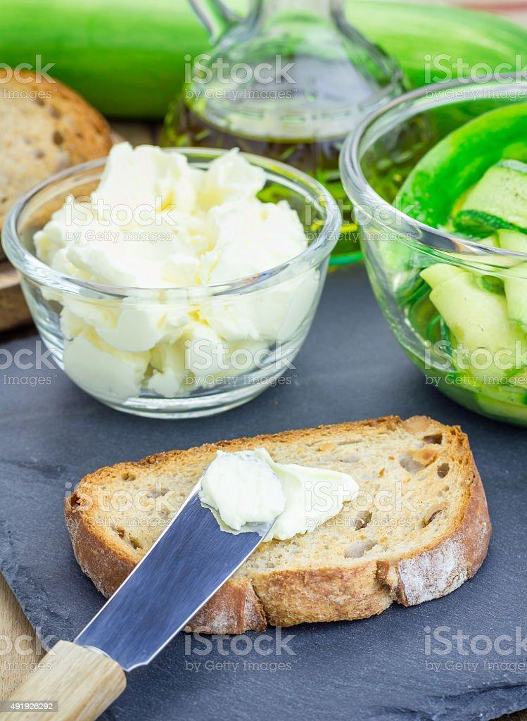 Making soft cheese and zucchini bruschetta stock photo