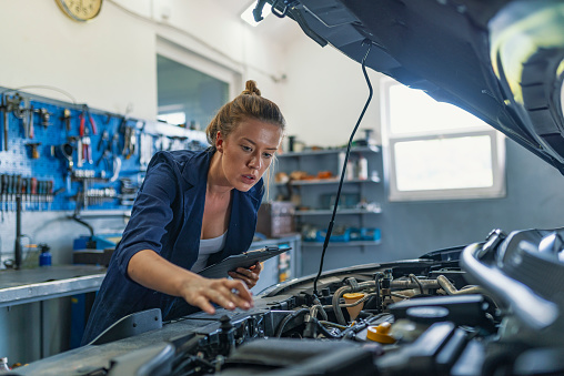 Female mechanic working on car. A Mechanic woman working on car in her shop. Technician woman working in auto repair workshop. Mechanic repairs the engine of a car in her workshop.