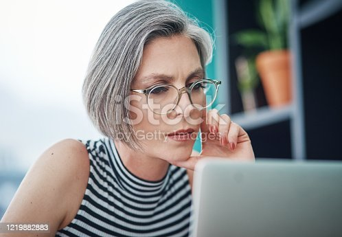Shot of a mature businesswoman using her laptop while sitting at her desk