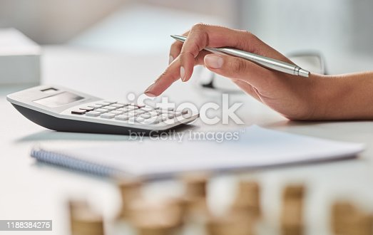 Cropped shot of an unrecognizable businesswoman working out her finances with a calculator and a notepad in her office