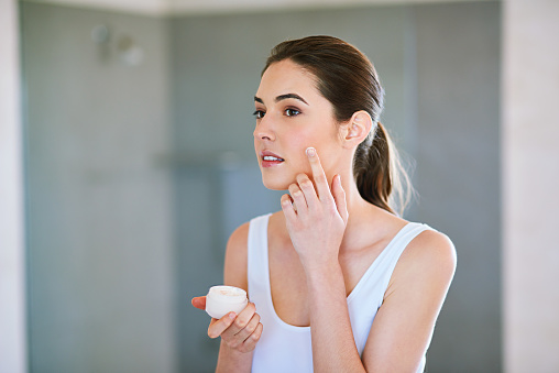 An attractive young woman applying cream to her face