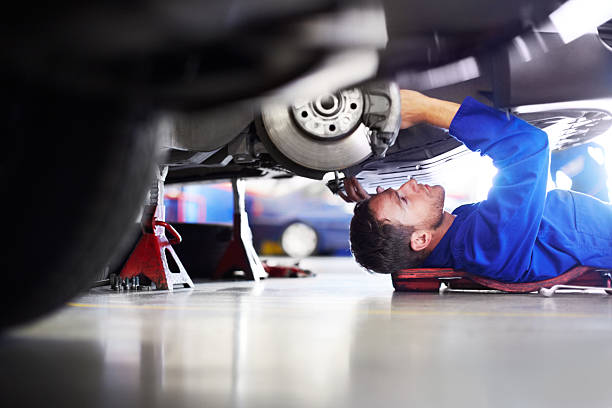 Making sure it's 100 percent road worthy A car mechanic working on the underside of a car mechanic stock pictures, royalty-free photos & images