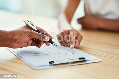 Closeup shot of two unrecognizable businesspeople going through paperwork in an office