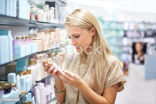 A young woman reads the information on a bottle of lotion