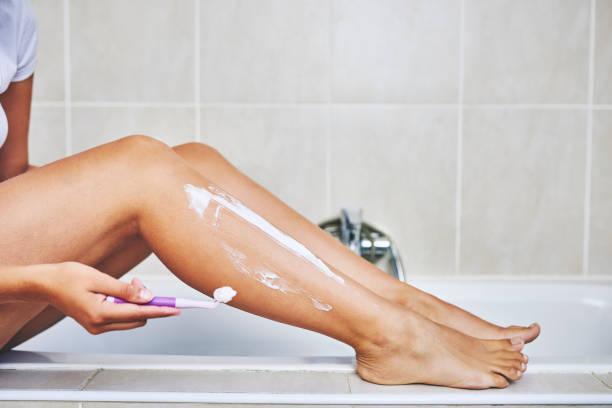 dafür zu sorgen, dass sie seidig glatte beine hat - bein tag routine stock-fotos und bilder