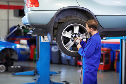 A mechanic torquing the lug nuts of a wheel with a wrench