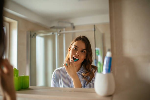 Making sure they'll stay clean all day Portrait of a beautiful young woman brushing teeth in the bathroom. toothbrush stock pictures, royalty-free photos & images