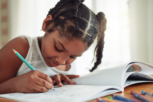 Cropped shot of a young girl coloring in at home