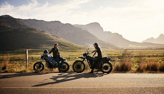 Shot of two young women riding their motorcycles through the countryside