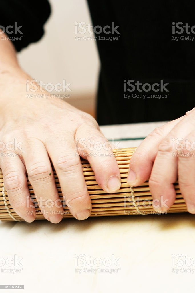 Making Sushi with a Bamboo Roller royalty-free stock photo