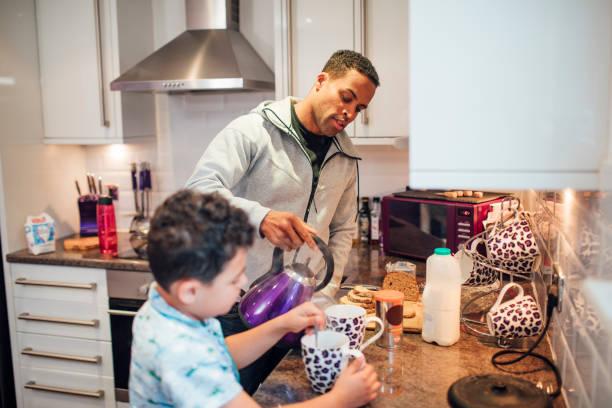 hacer té con papá en la mañana - padre que se queda en casa fotografías e imágenes de stock