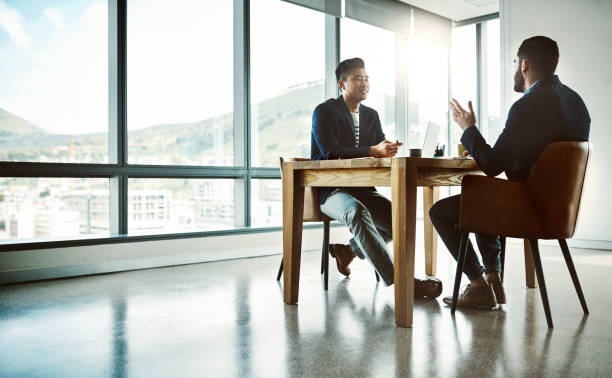 Making that million dollar pitch Shot of two young businessmen having a discussion at a desk in a modern office military recruit stock pictures, royalty-free photos & images
