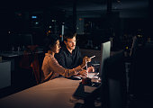 Shot of two businesspeople working late in an office