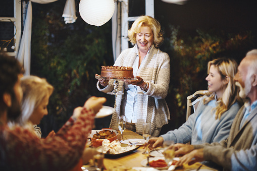 Family celebrating Thanksgiving together. Senior woman serving chocolate cake to her family.