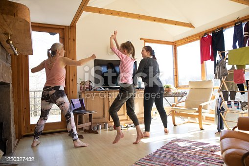 Mature Caucasian female exercising in front of the TV with her daughters in the living room during the lockdown.