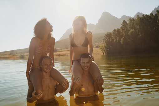 Shot of a group of friends enjoying a playful moment during a swim at the lakehttp://195.154.178.81/DATA/i_collage/pu/shoots/785123.jpg