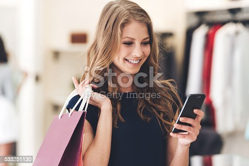 Beautiful young woman with shopping bags using her smart phone with smile while standing at the store