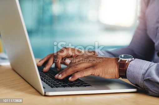 Closeup shot of an unrecognizable businessman using a laptop in an office