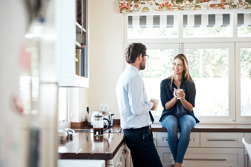 Shot of a young couple having coffee together in the kitchen at home