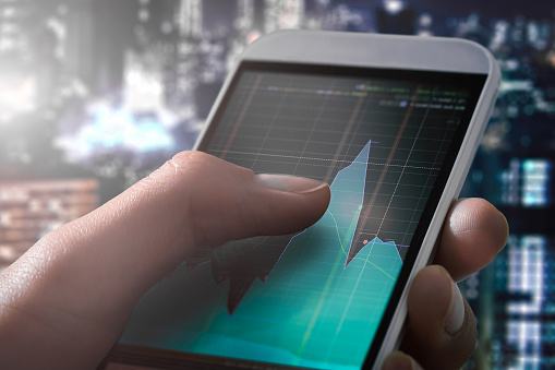 1044507110 istock photo Making trading online on the smart phone in hand. 843017314