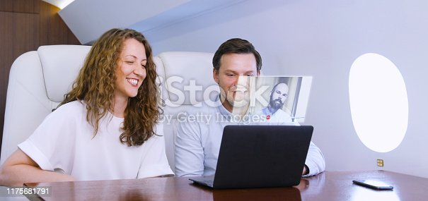 1141355850istockphoto Making video call on private plane 1175681791