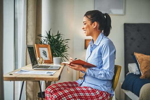 Shot of a young woman having a video call with her colleague while working from home