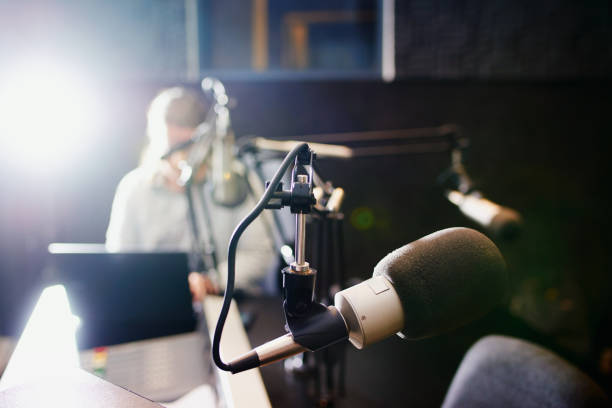 Making waves over the airwaves Shot of a microphone in a recording studio with the presenter blurred in the background radio dj stock pictures, royalty-free photos & images