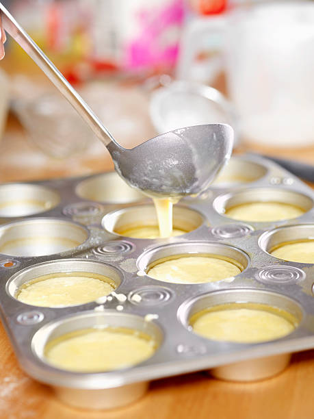 Making Yorkshire Pudding Making Yorkshire Pudding -Photographed on Hasselblad H1-22mb Camera muffin tin stock pictures, royalty-free photos & images