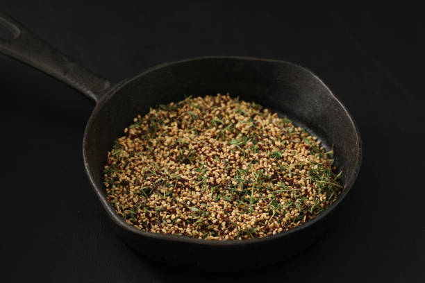 Making Za'Atar A high angle close up horizontal photograph of Za'Atar in a small black cast iron pan. Isolated on black. zaatar spice stock pictures, royalty-free photos & images