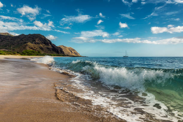Makua beach view of the wave with beatiful mountains and a sailboat in the background, Oahu island, Hawaii stock photo