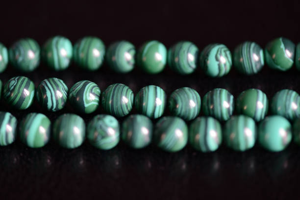 Malachite stone beads necklace on a dark background close up Malachite stone beads necklace on a dark background close up malachite stock pictures, royalty-free photos & images