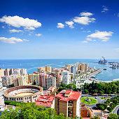 Malaga cityscape with Bullring of La Malagueta and harbor, Spain. Composite photo