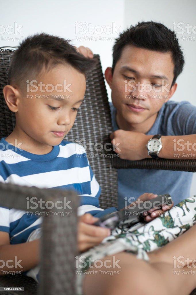 Malaiische Vater mit seinem Sohn Handheld-Spiel - Lizenzfrei Alleinerzieher Stock-Foto