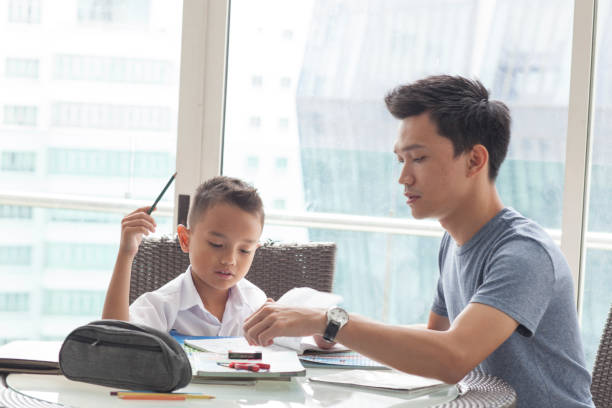 Malay male with young boy doing homework A Malay father with his son in school uniform at the dining table doing homework illiteracy stock pictures, royalty-free photos & images