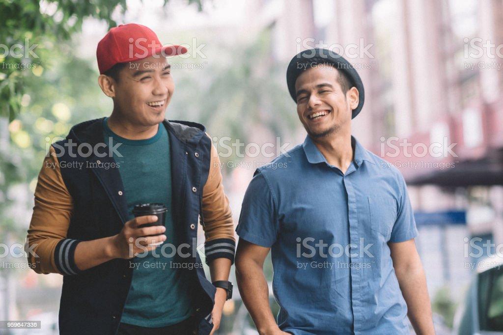 2 machos malayos con sombrero, hablando y caminando en la calle - Foto de stock de Adulto libre de derechos